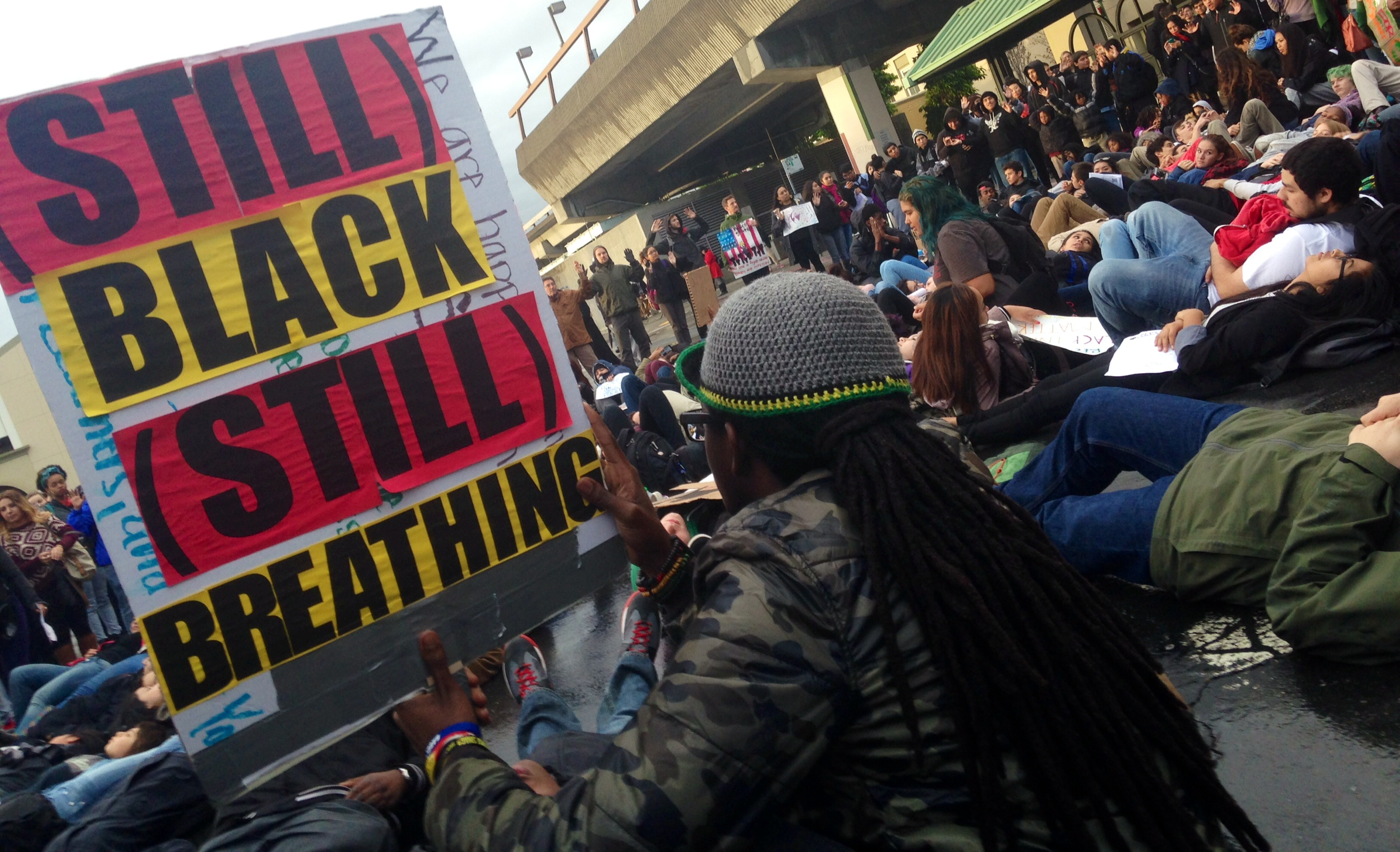 """Oakland students staged a """"die-in"""" outside the Fruitvale Station Monday evening in support of the growing movement Black Lives Matter."""
