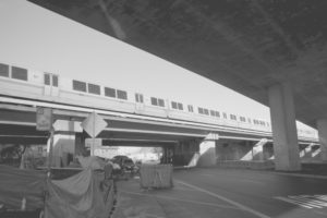 A BART train runs adjacent to the freeway underpass - above a homeless camp on Northgate St.
