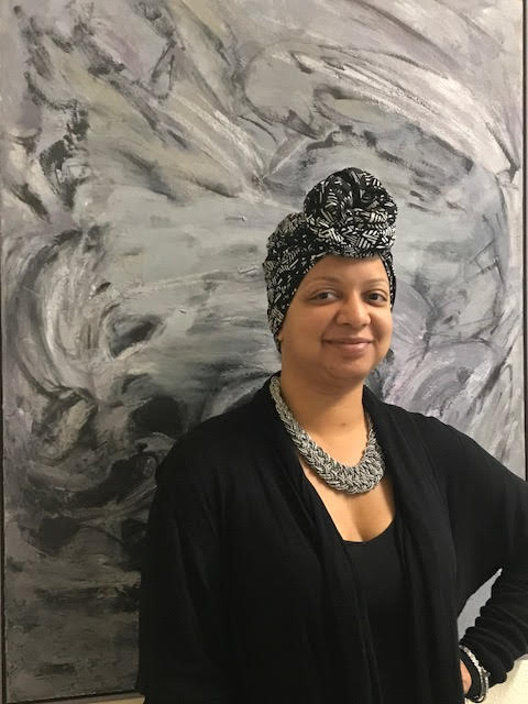 An African American woman wearing a grey head wrap and black cardigan poses in front of a grey marble like background for her portrait.