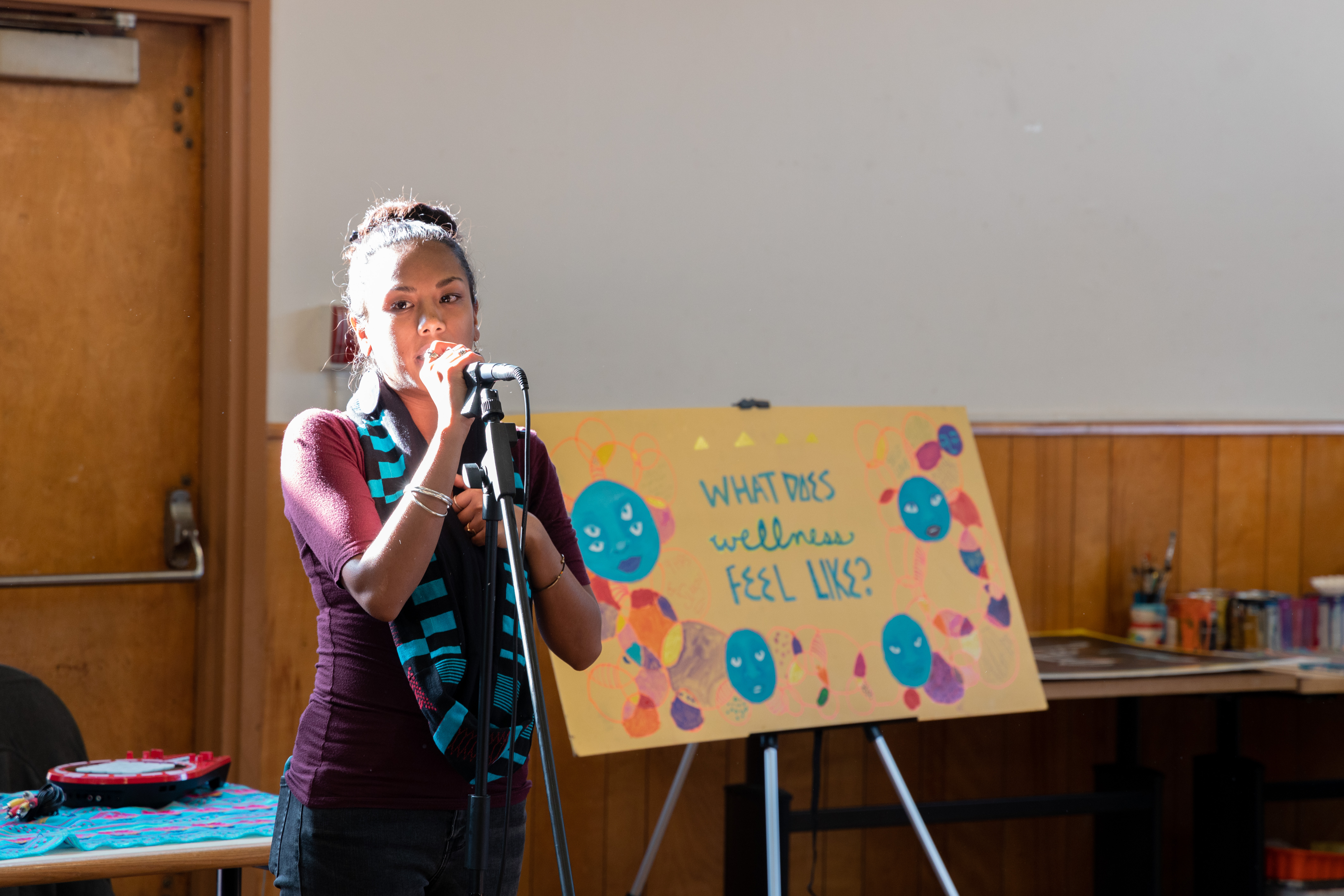 """A young indigenous woman with her hair in a bun speaks in a microphone at a well-lit room. A sign behind her says """"What Does Wellness Feel Like?"""""""