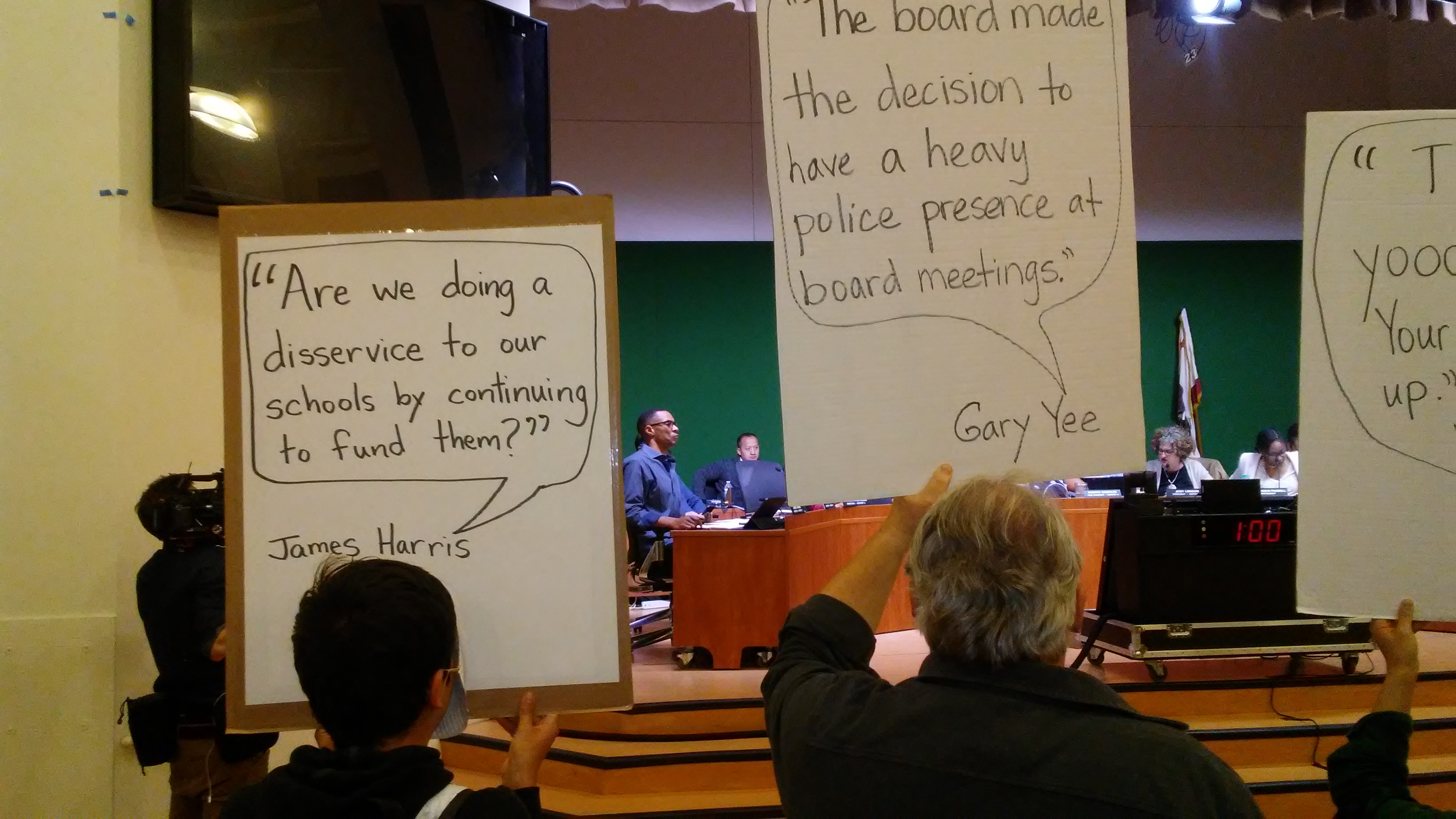 At last week's Oakland School Board meeting, Board member James Harris, one of four incumbents who will not run for re-election this year, listens to District Finance staff present their recommendations for over $20 million in budget cuts for next year. Oakland Not For Sale Protesters, holding signs in the foreground, changed their tactics, remaining silent so that the Board could not use them as an excuse to conduct public business in private.