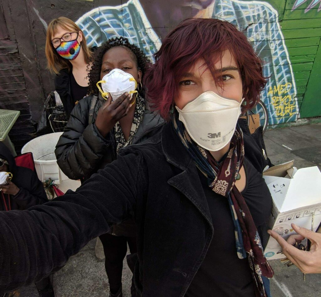 Photo: Three Mask Oakland volunteers wearing respirator masks pose for a group selfie.