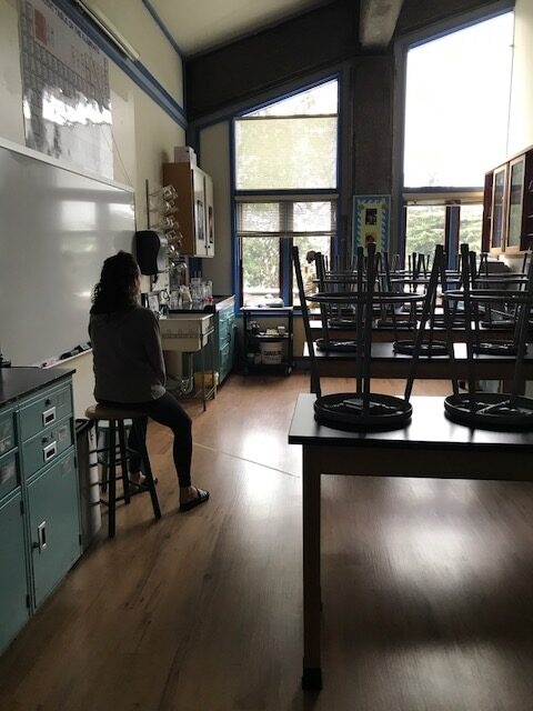 A dark image of a high school classroom that is empty except the teacher.