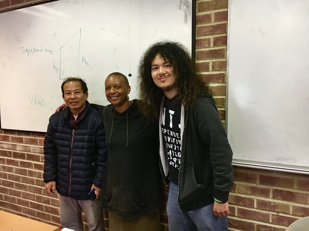 Three people line up in front of a whiteboard to take a photo: an elder Asian American man, an African American woman college instructor, and a young man with long hair.
