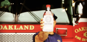 "A firefighter is holding a glass container of hand sanitizer. In the back is a bright red firetruck that says ""Oakland Fire Dept."""