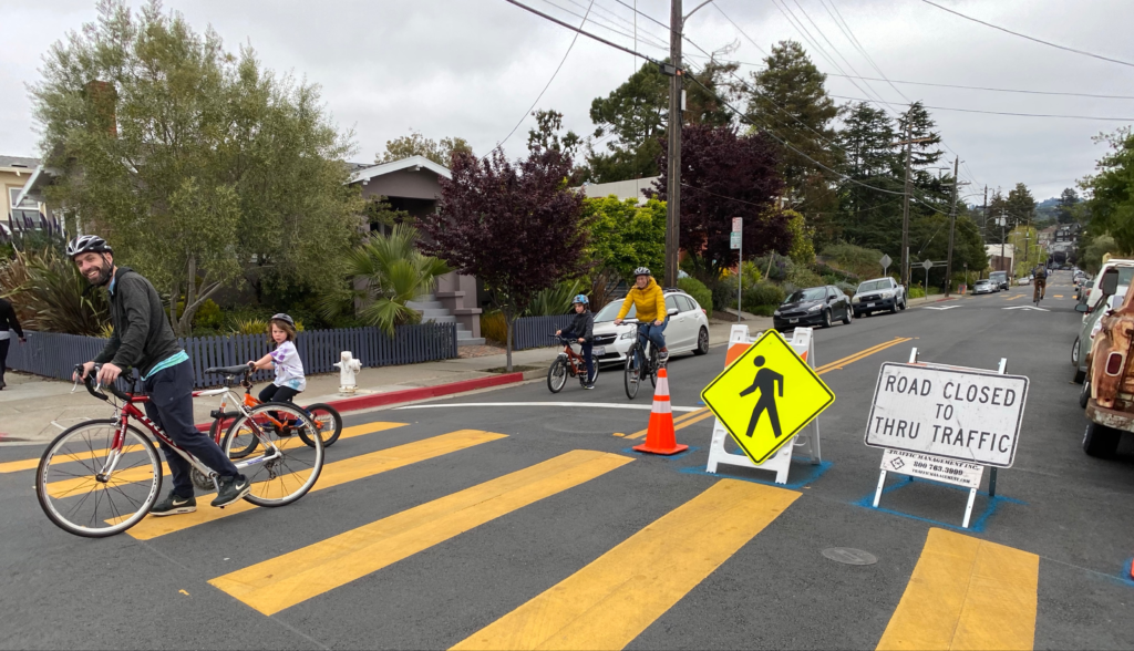 Residents ride bikes near closed street.