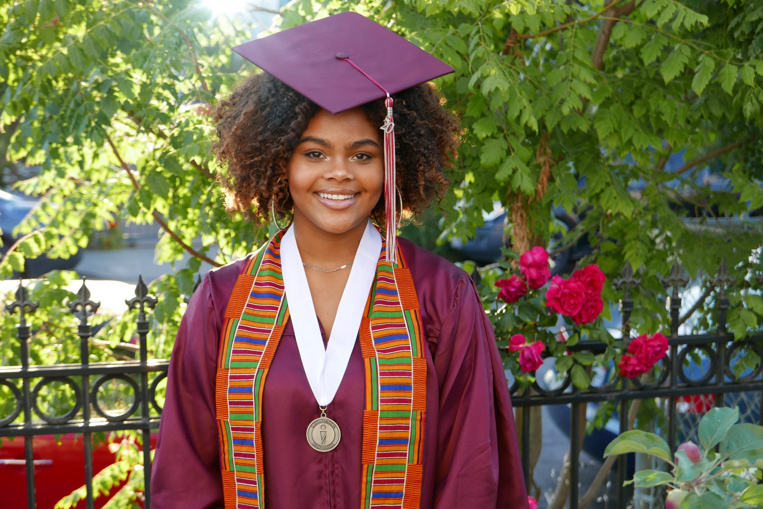 A smiling African American teenager wearing a maroon cap and gown smiles for the camera.
