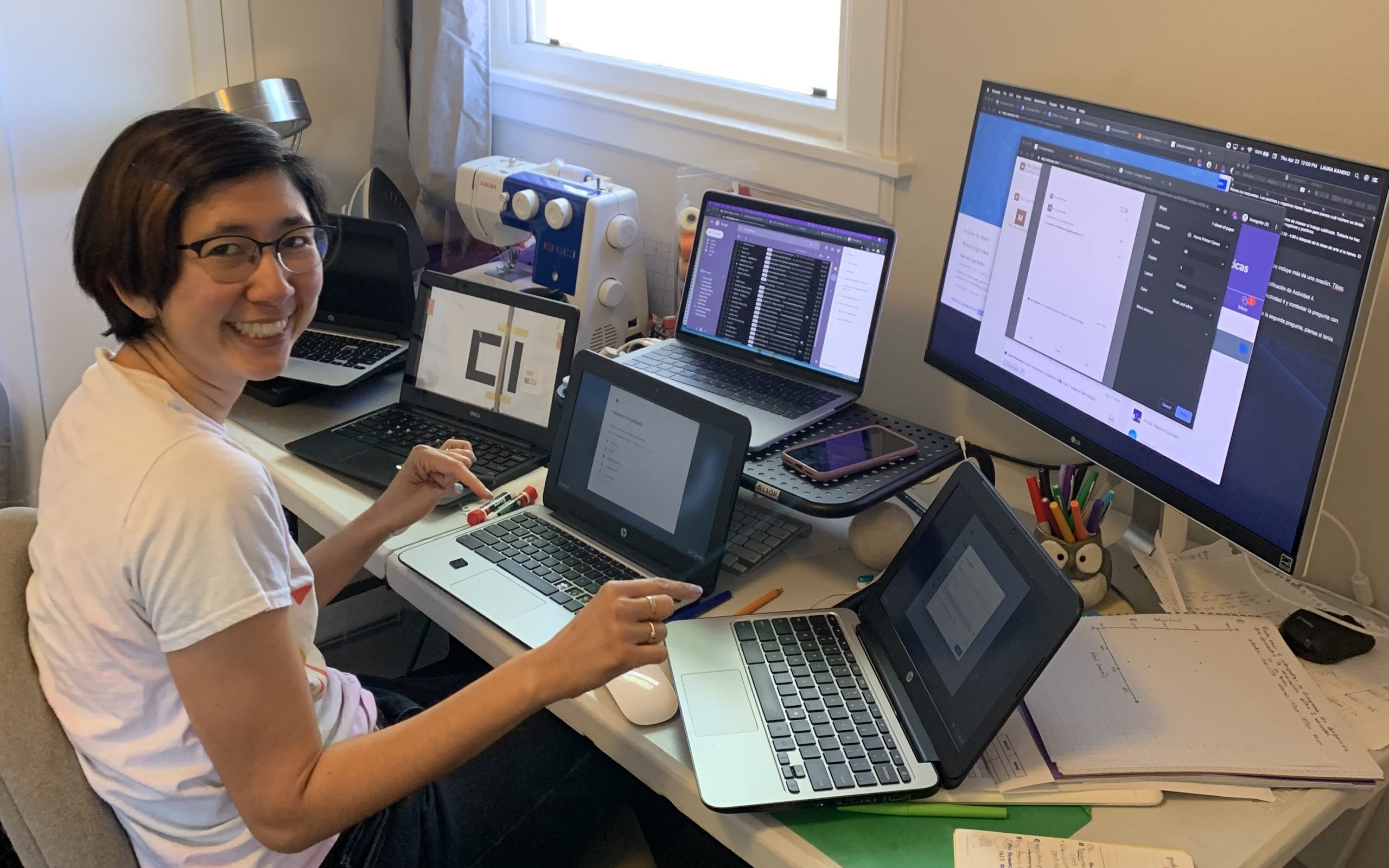 A smiling East Asian woman with a bob haircut and glasses is sitting at a large desk with several Chromebook laptops in front of her, plus a big monitor.