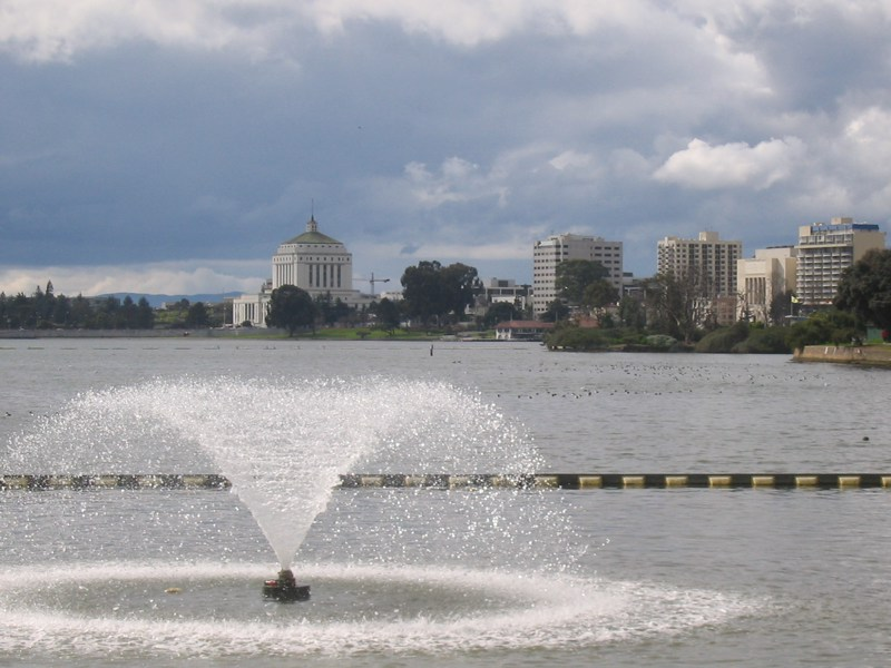 An image of a peaceful, flat lake with a fountain in it.