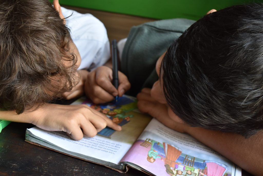 A bird's eye view of two children reading a textbook.