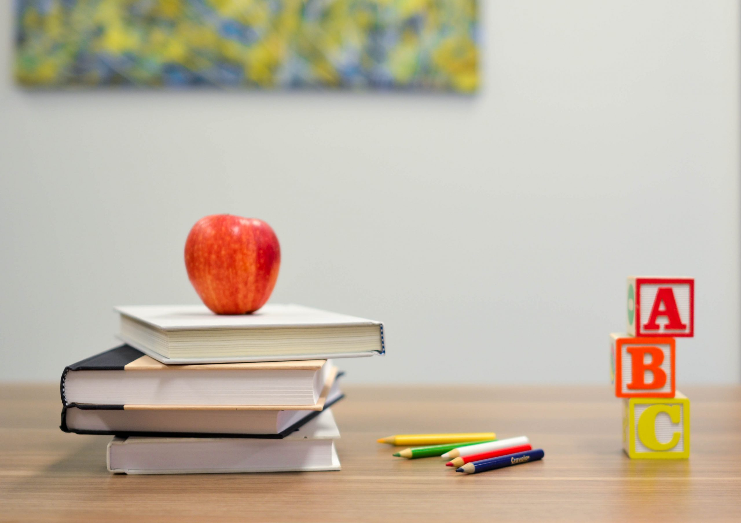 An image of a desk with a few books, an apple, and ABC blocks