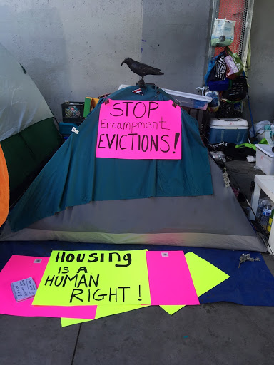 "An image of a tent with the words ""Housing is a Human Right"""