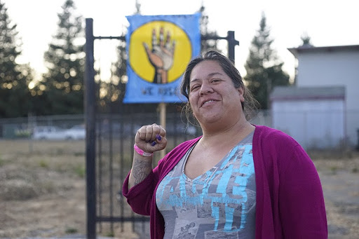 A woman smiles and holds up one fist in front of a housing encampment in East Oakland.