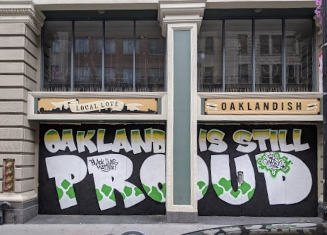 "A mural says ""Oakland is still proud"" in big letters."