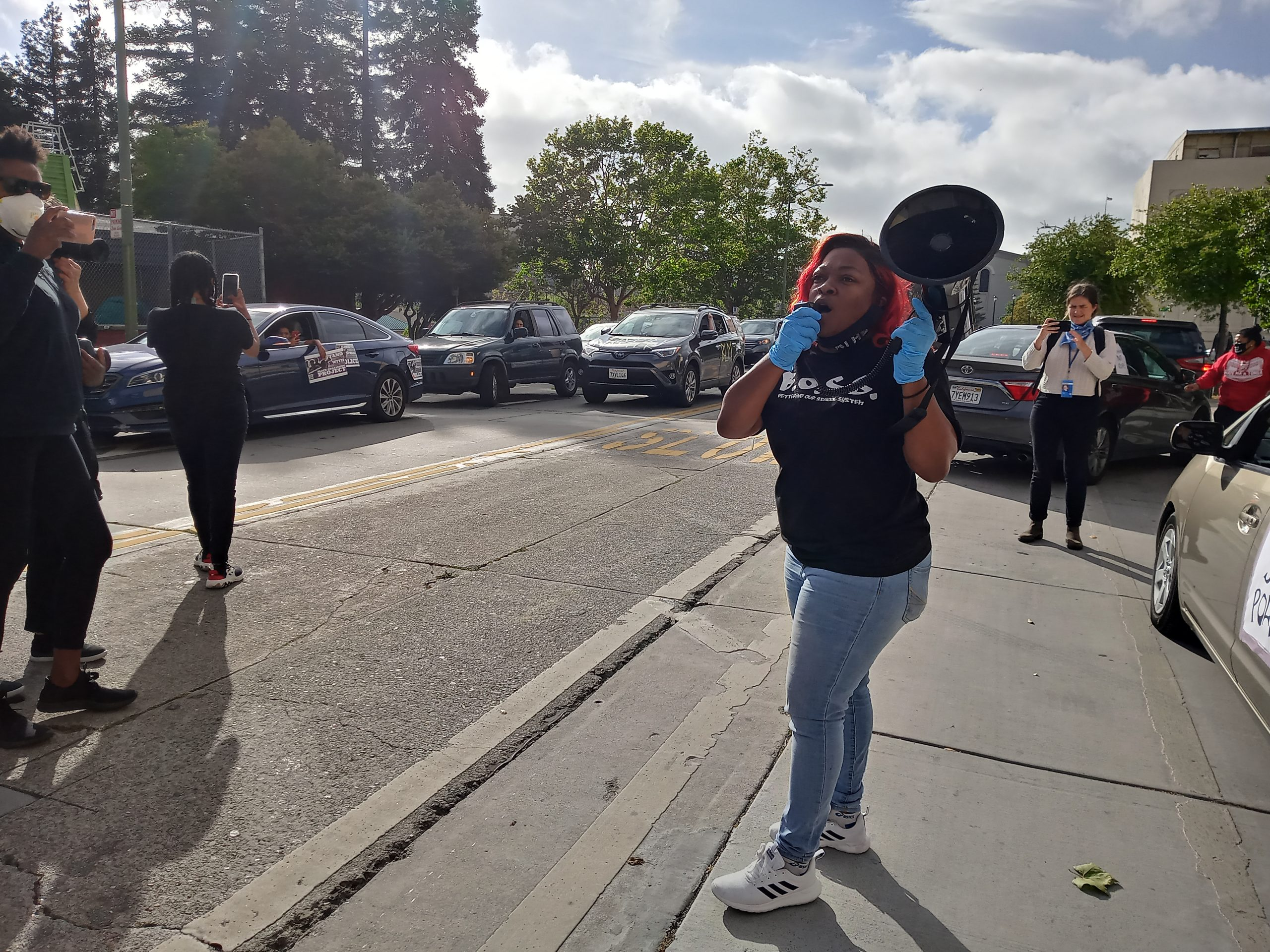 An image of an African American woman speaking into a megaphone from a sidewalk