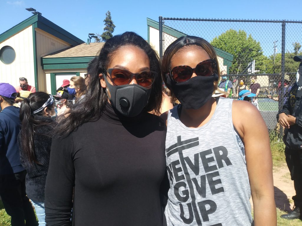 Two Black women wearing black face masks stand next to each other and pose for a photo. The sun is bright.