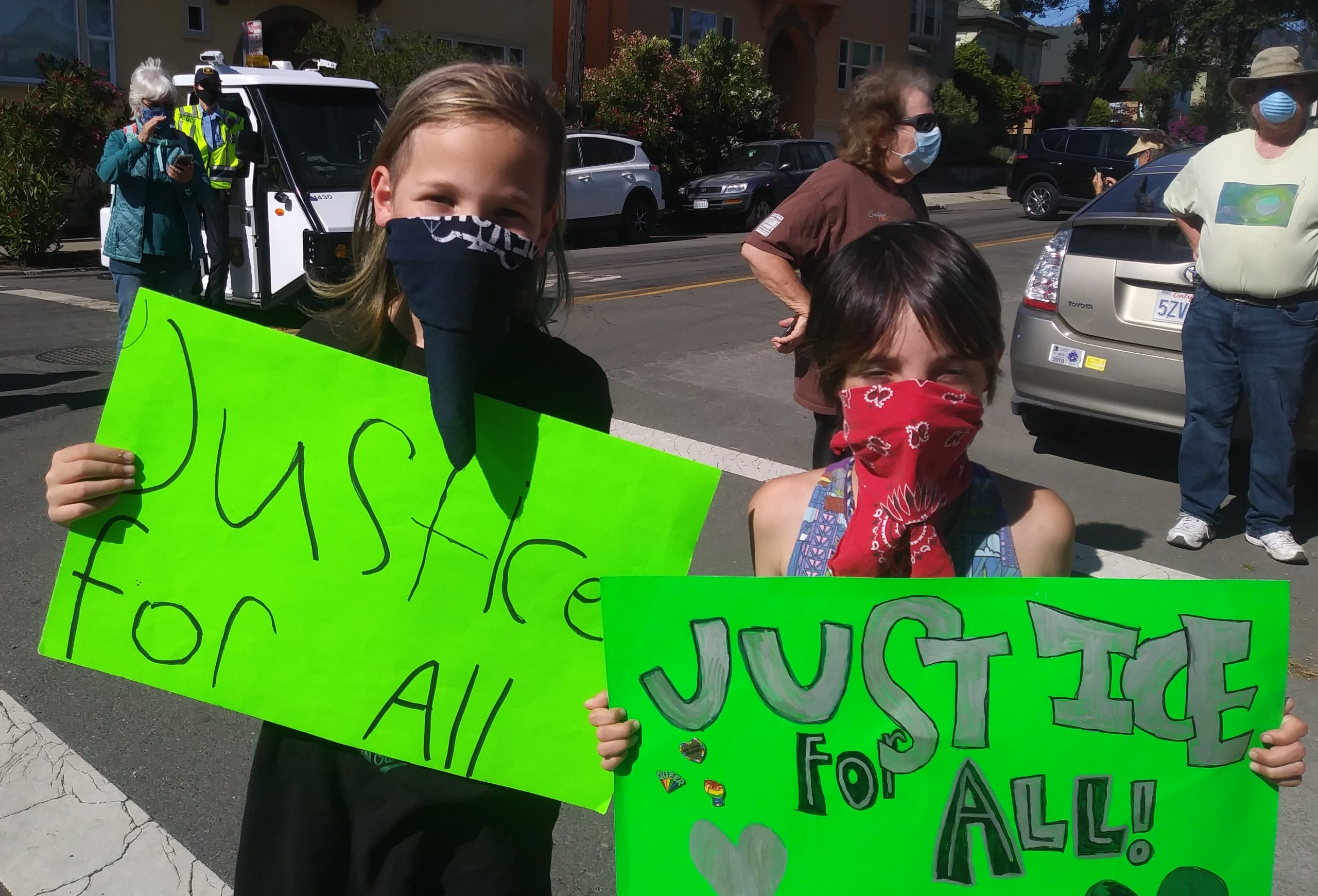 "Two children wearing masks hold up handmade signs that say ""justice for all."""