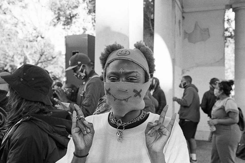 An image of an African American youth organizer wearing a mask and smiling.