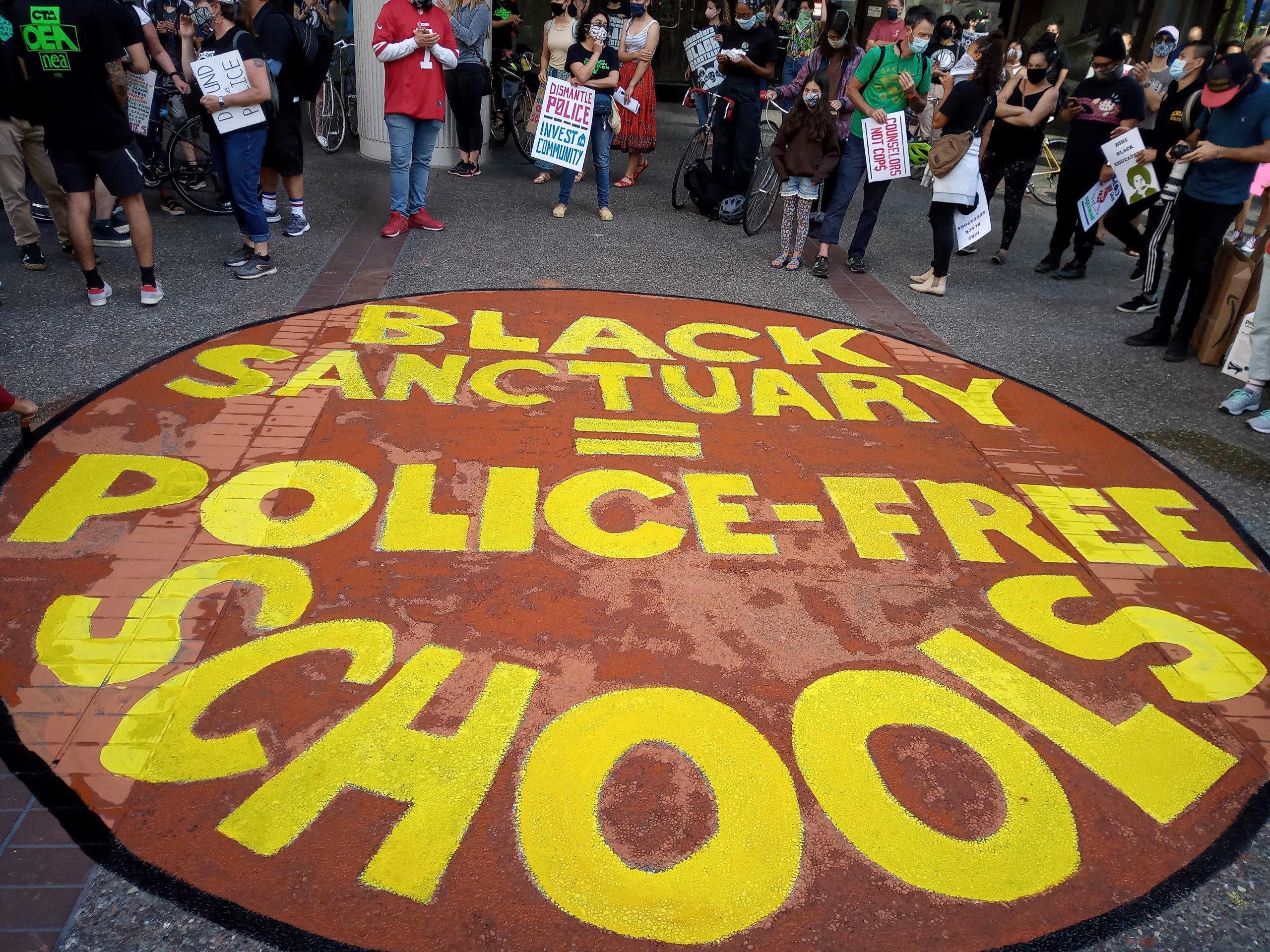 """A sign painted on the ground reads """"Black sanctuary = police-free schools"""" with people in masks behind the sign."""