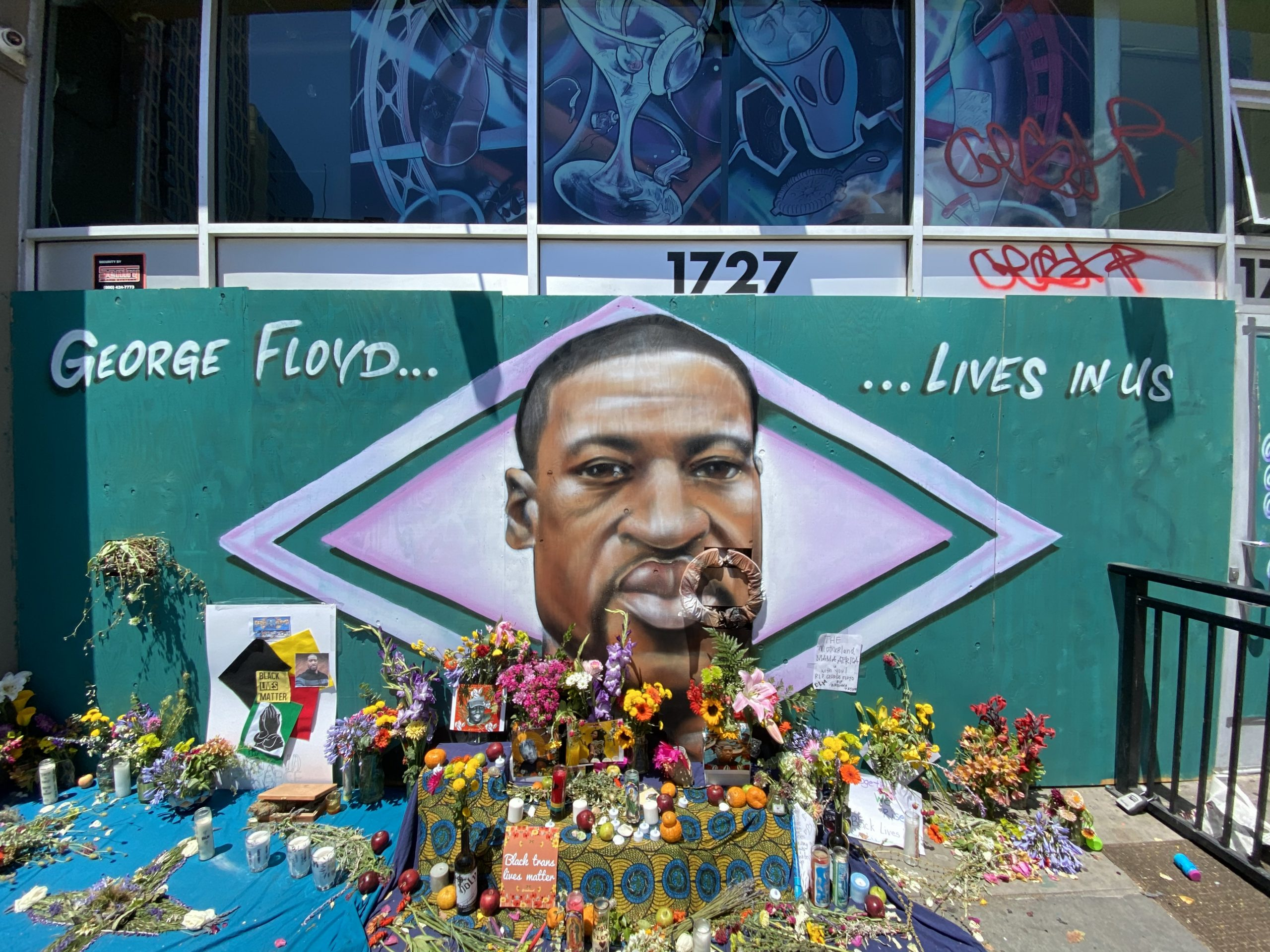 An image of an African American man at the center of a mural with a green background. Flowers are in front of it. It is an alter for the man who was killed by police.