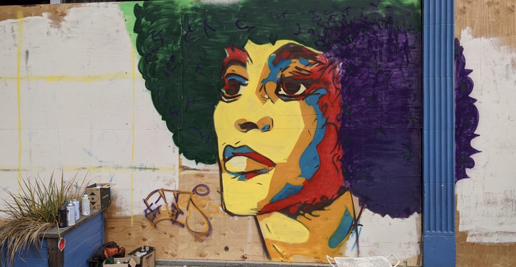 A mural of a black woman with an afro that is multihued.