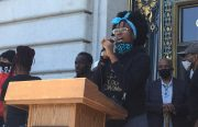 An African American teen girl, Alysia Reaves, speaks into a microphone behind a podium in front of SF City Hall.