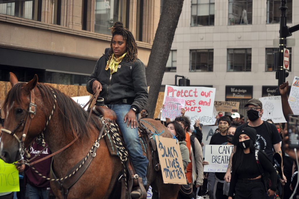 "An African American woman on a horse leads a part of the protest against police brutality. A sign that says ""Black Lives Matter"" is on the side of her horse."