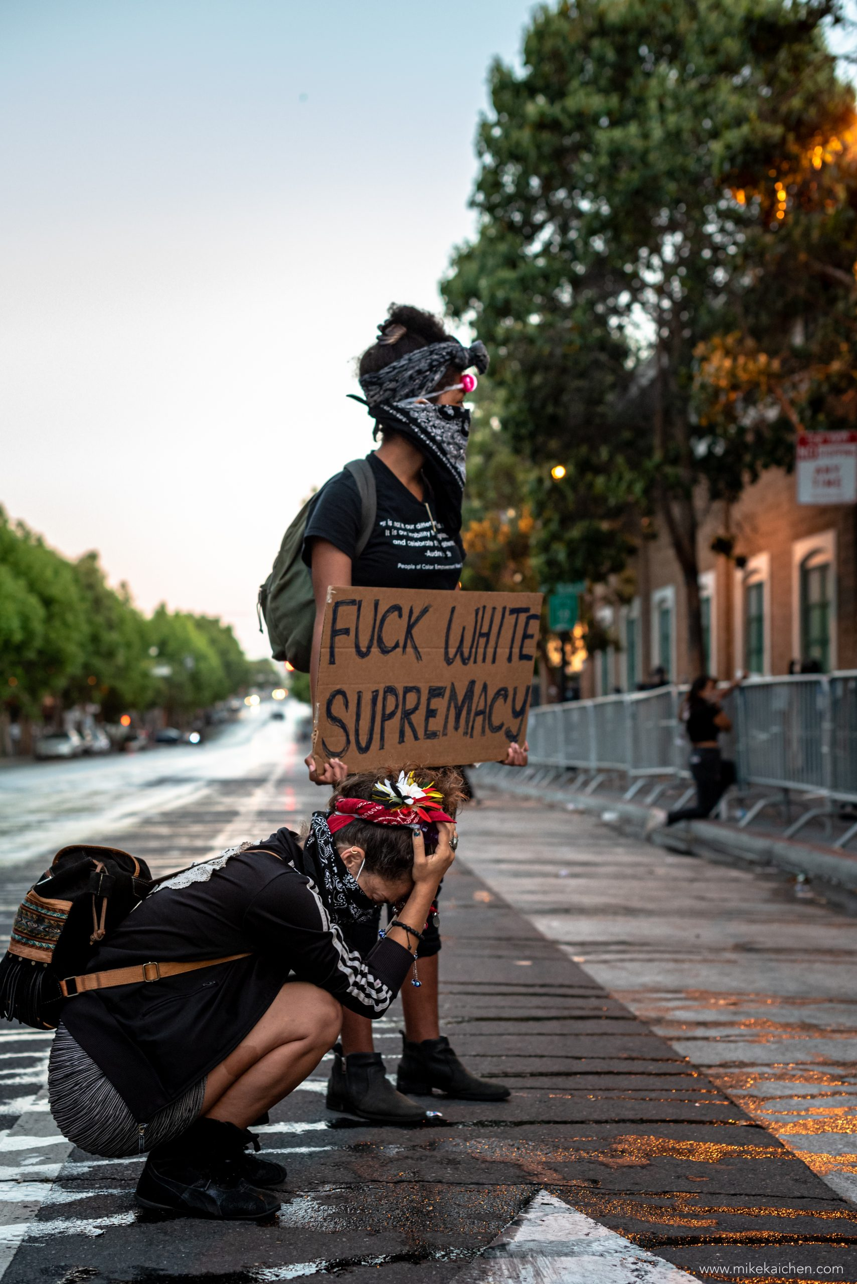 """Two women wearing bandanas hold protest signs. One sign says """"Fuck White Supremacy."""""""