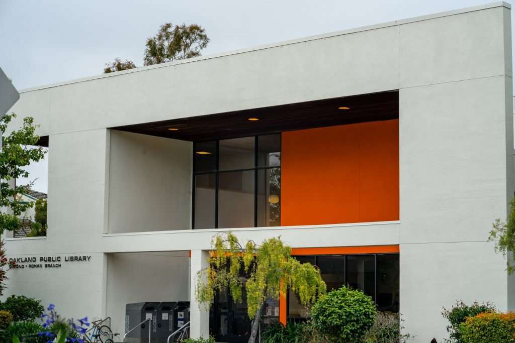 A image of the outside of a white and orange library in Oakland.