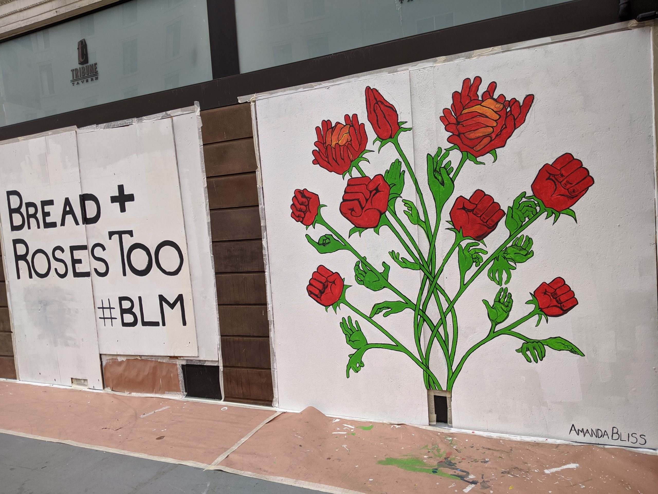 "A mural with a white background says ""bread and roses too BLM"" with an image of roses adjacent to it."