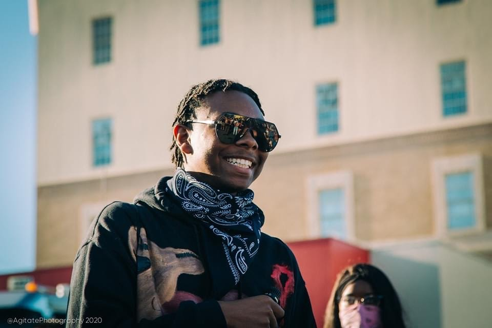 An image of a smiling African American youth who is wearing sunglasses and a bandana around his neck.