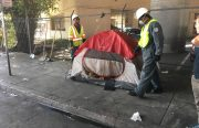 Two city workers remove a curbside tent.