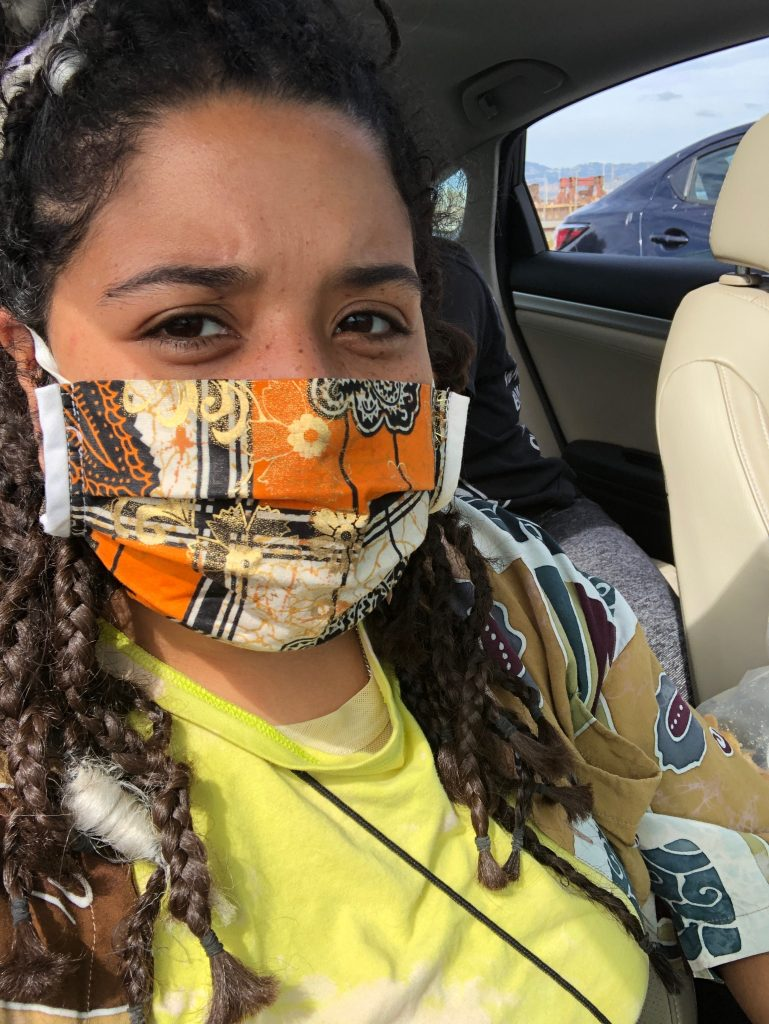 A biracial woman with braids sits in a car during a protest and is wearing a colorful orange and black mask.