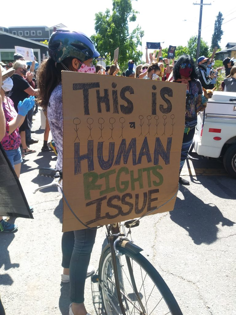 "A cardboard sign is held up by someone new to a bike. The sign says ""This is a human rights issue."""