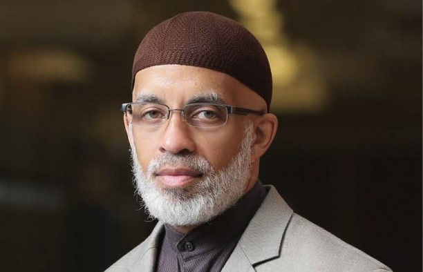 An African American man with a grey beard, glasses, and brown crocheted cap looks at the camera for a portrait.