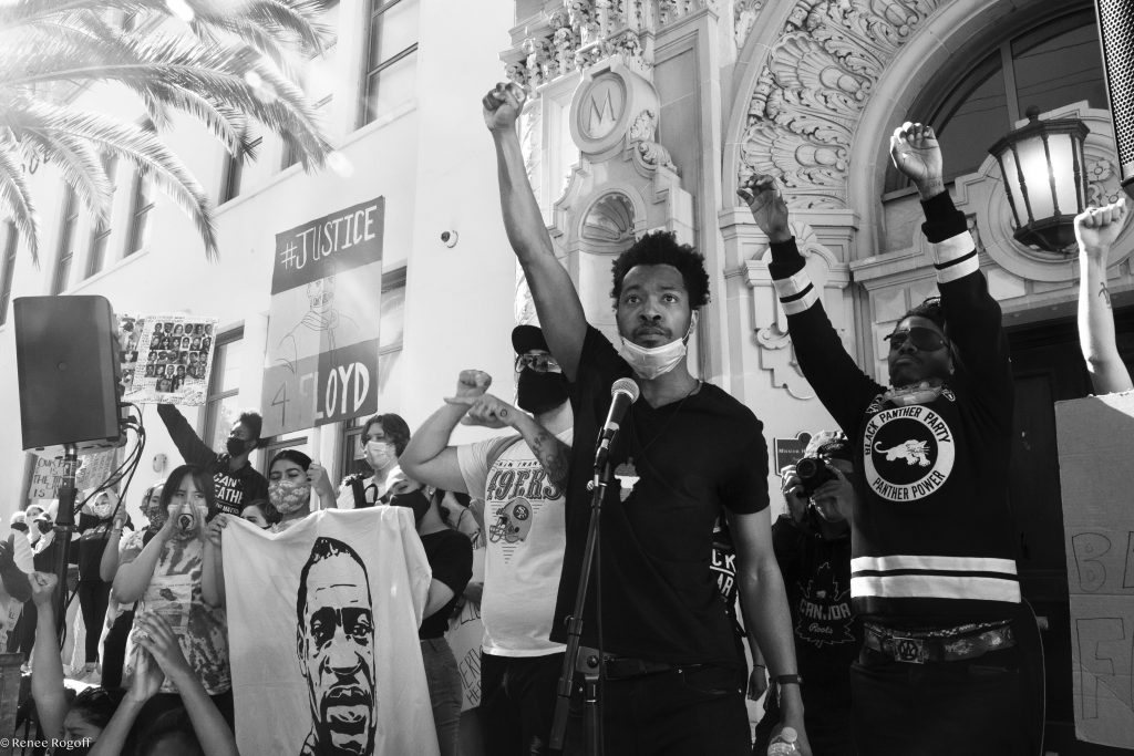 A Black man raises his fist in the air in front of an ornamental building. The photo is in black and white.