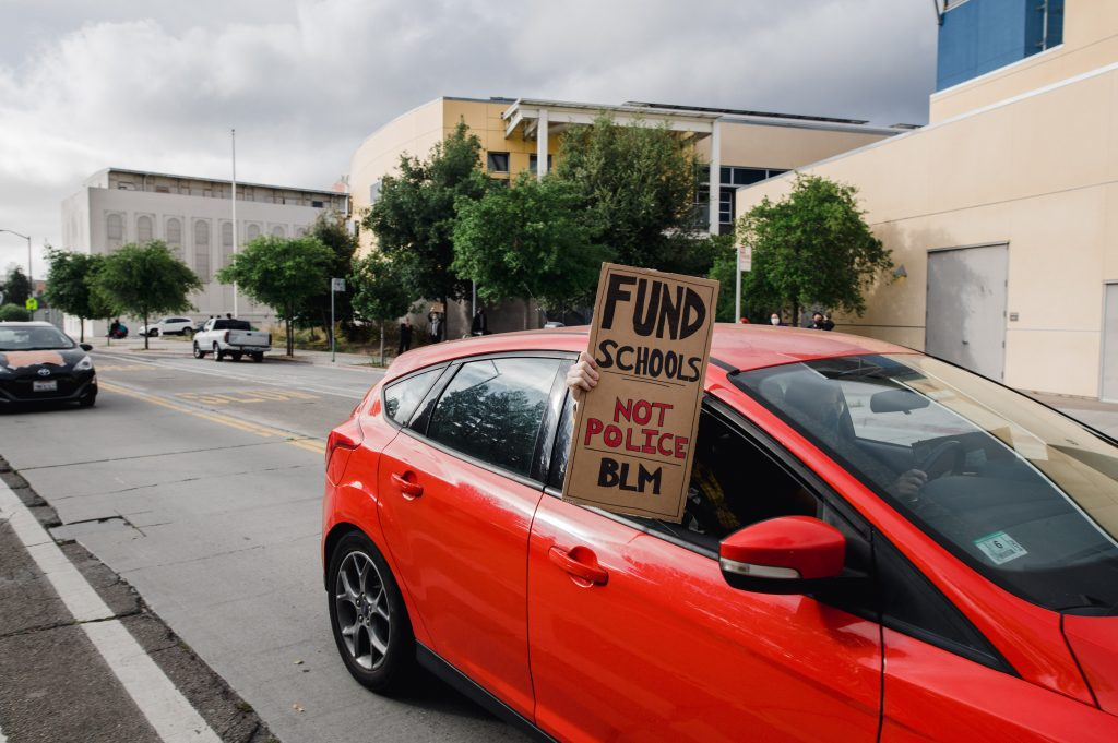 "A red car has the window open. A hand is holding a homemade cardboard sign that says ""Fund Schools Not Police BLM"""