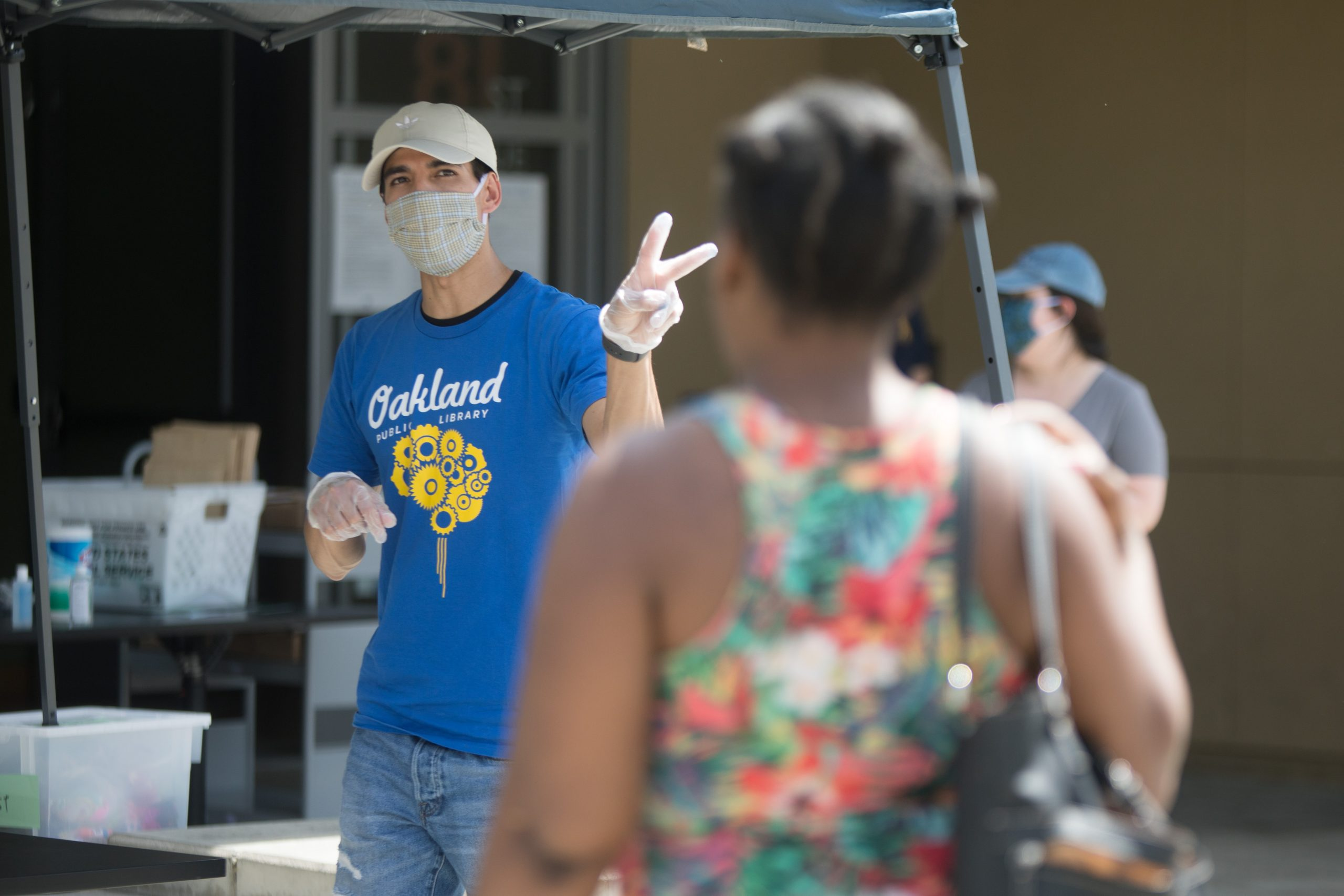 A man wearing a mask holds up the peace sign as he's handing out food bags from a library branch in East Oakland.