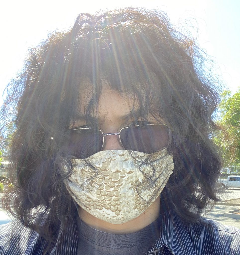 A young man wearing a mask and sunglasses with long curly hair.