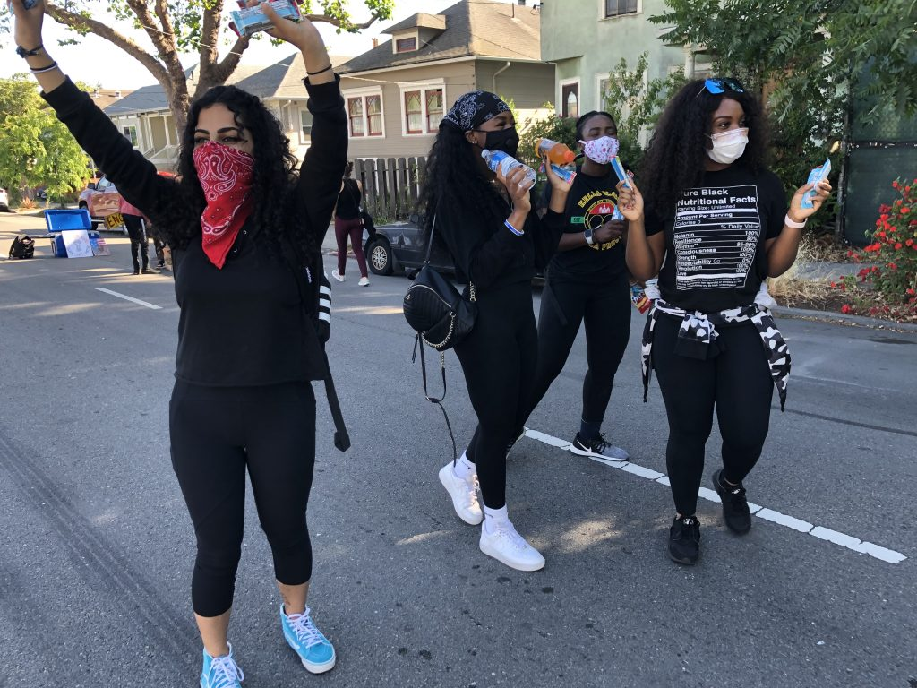 Several young women wearing black and with bandanas look happy and are passing out free water bottles on the street during a protest in Berkeley.