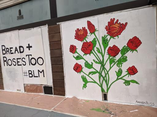 """A mural with a white background says """"bread and roses too BLM"""" with an image of roses adjacent to it."""