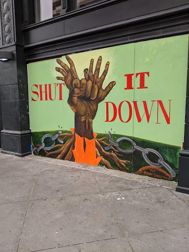 "An image of two hands tied together with ""shut it down"" behind it."