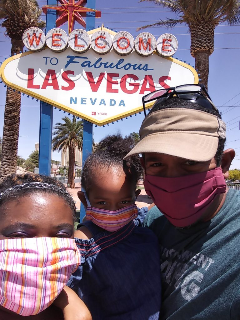 An image of a beautiful African American family (parents and young toddler girl) in front of a Las Vegas sign/marquee.