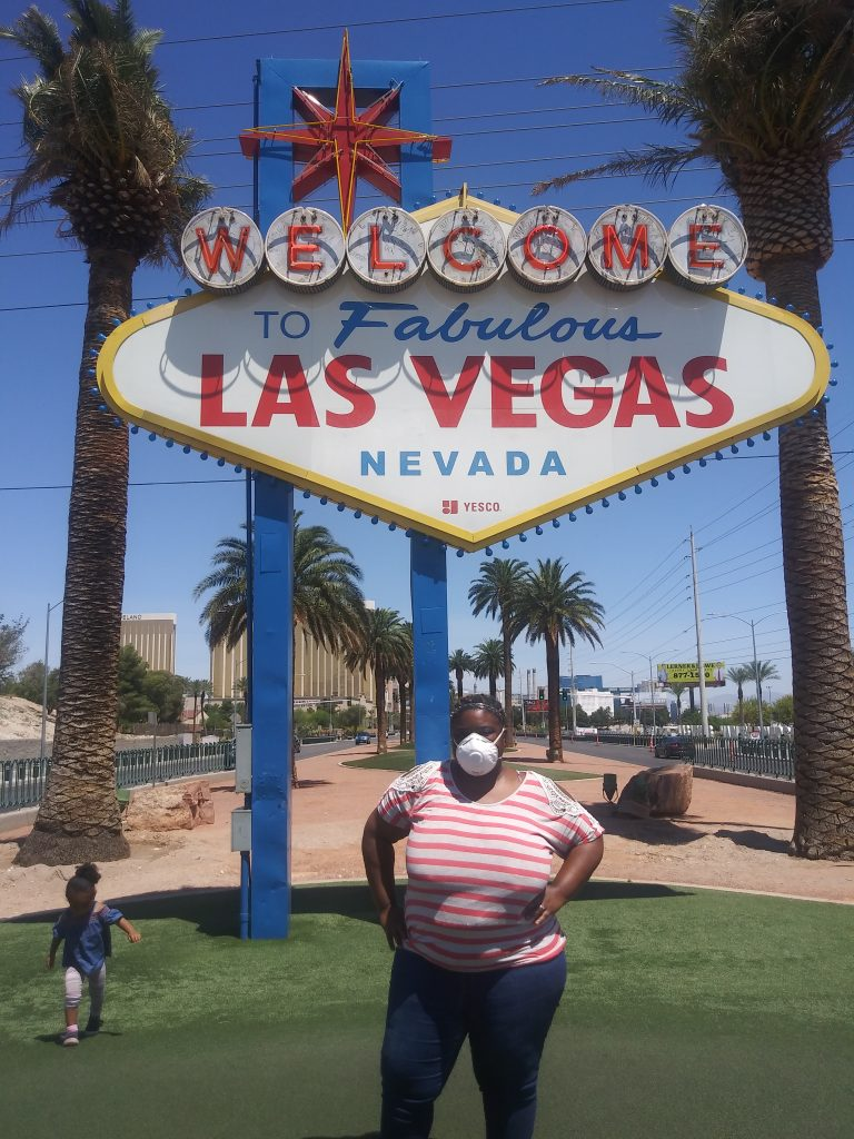 An African American woman stands in front of the Las Vegas sign, with a child running in the background