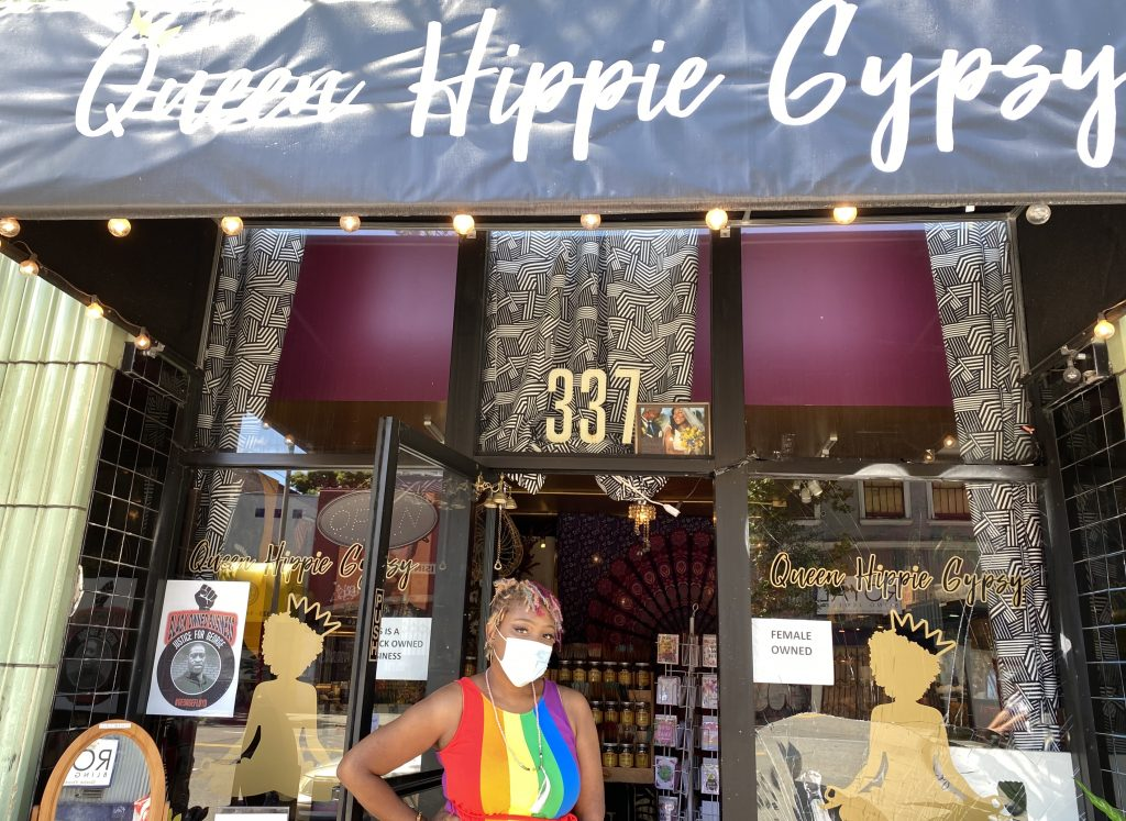 An African American woman wearing a rainbow colored dress stands in front of a storefront in Oakland.