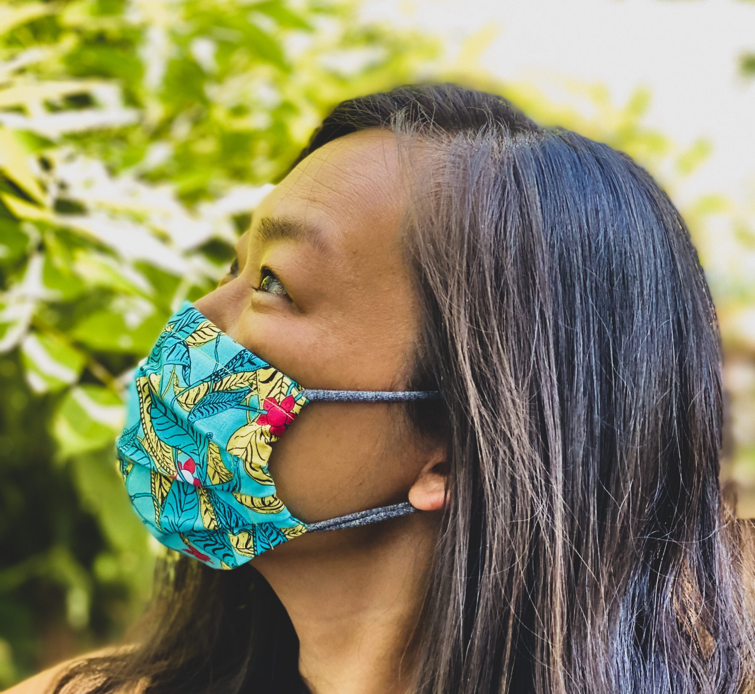 An Asian American woman poses for a profile photo wearing a colorful green mask.