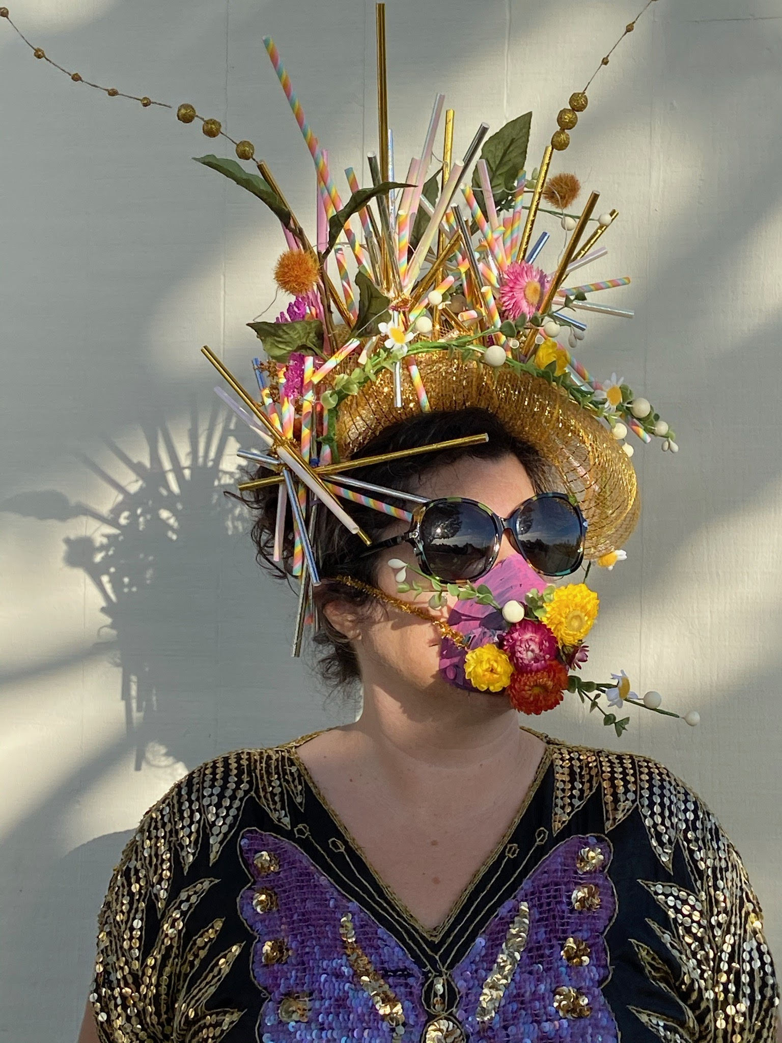 A woman wears a handmade crown made from flowers, and a mask that matches.