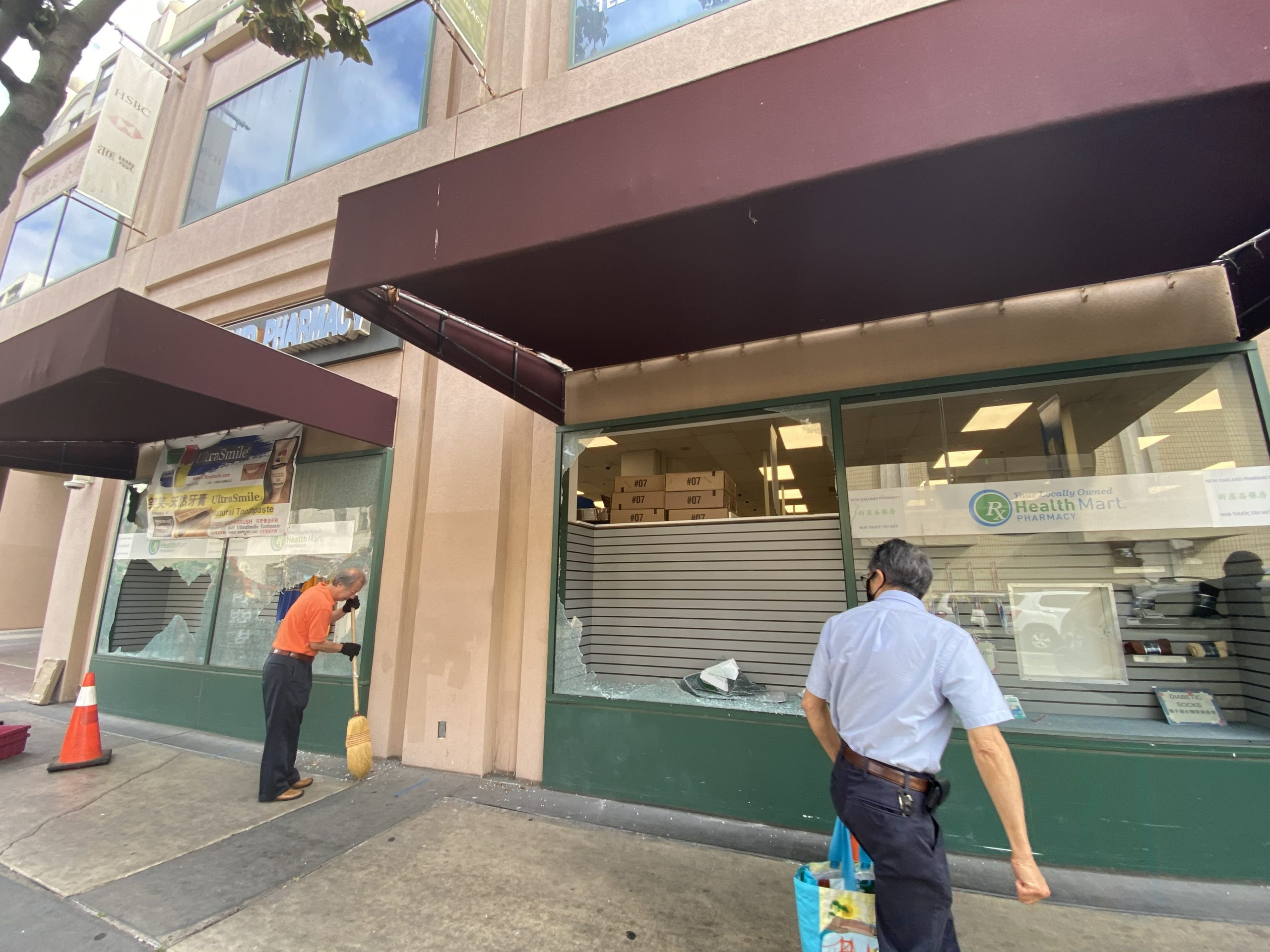 An image of a large window that is broken in Chinatown, with the owner sweeping up glass in the morning.