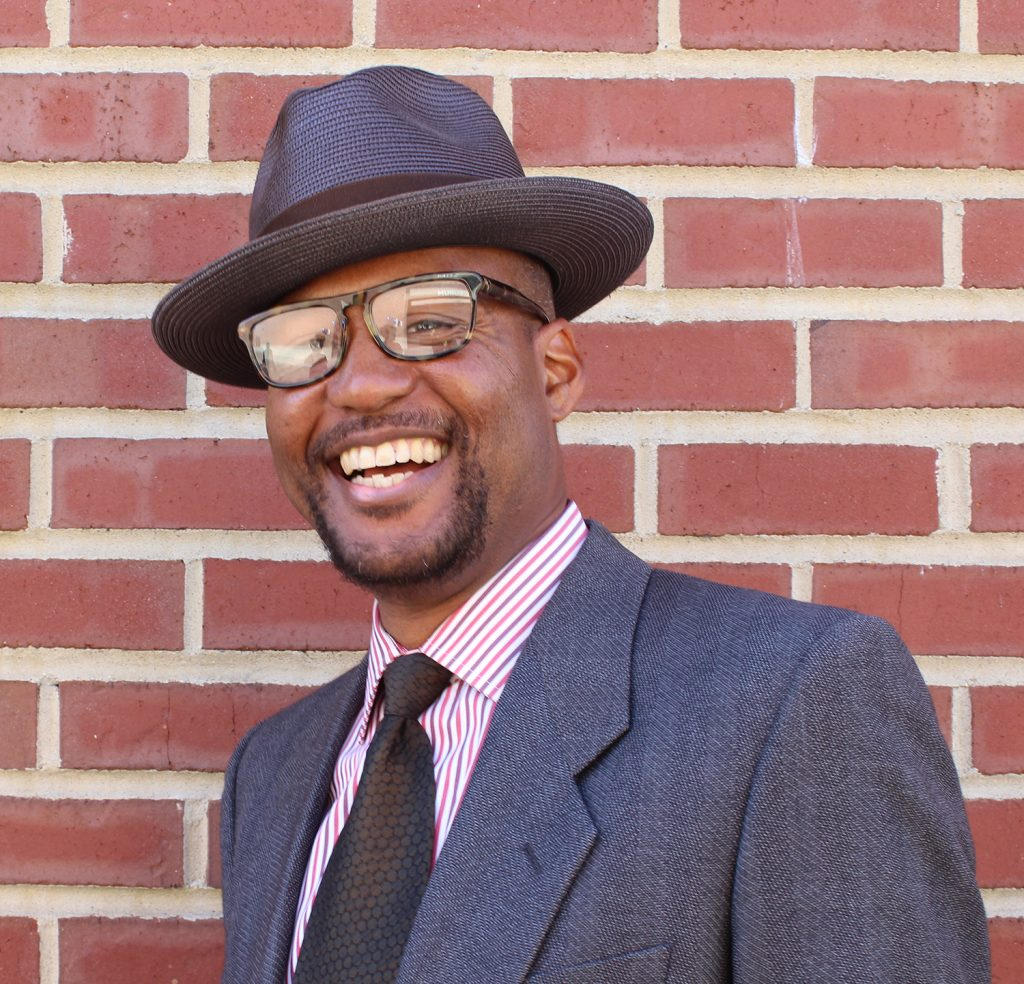 An African American man in glasses and a hat smiles in front of a brick background