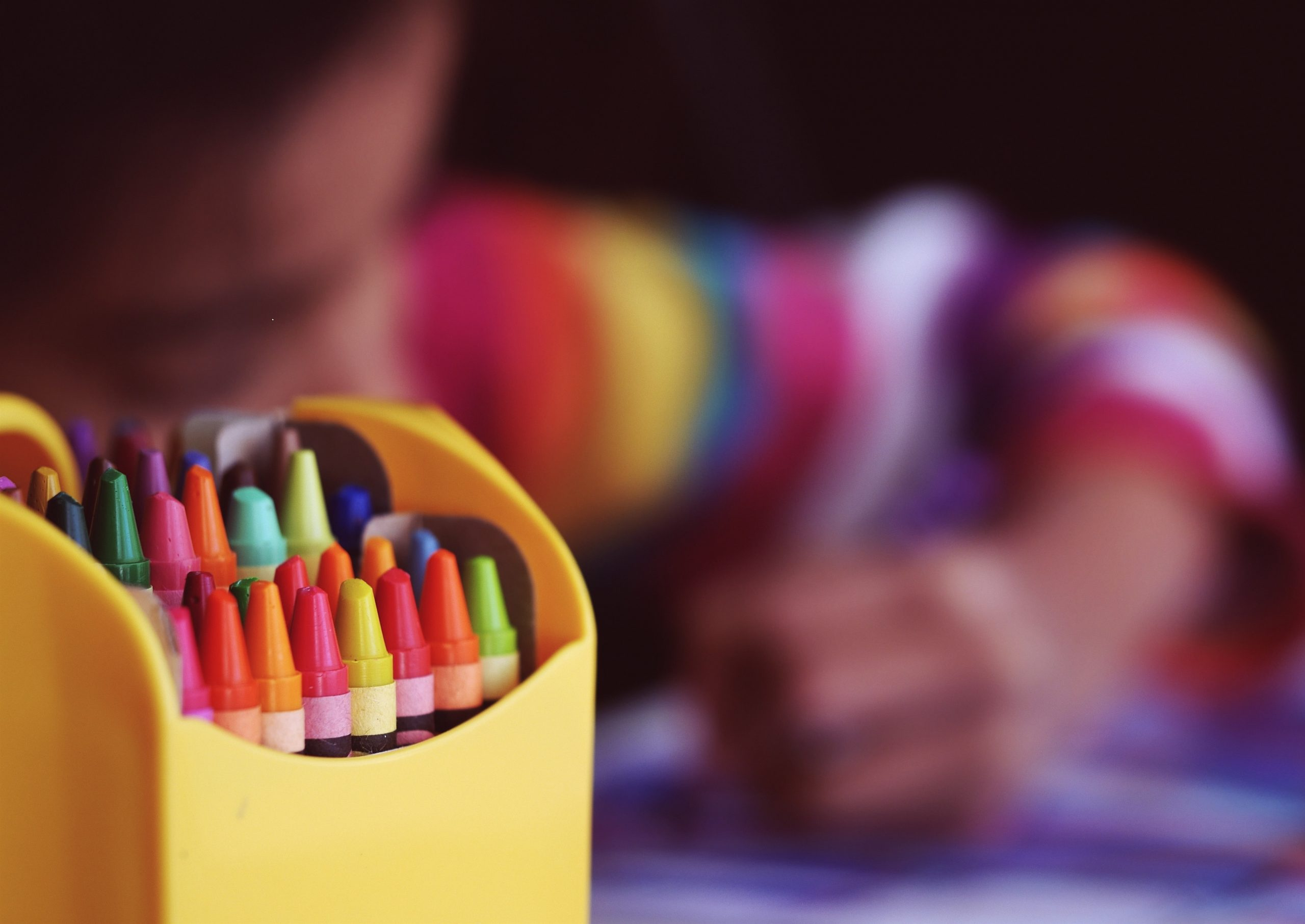 A closeup of crayons and a child in the background coloring.